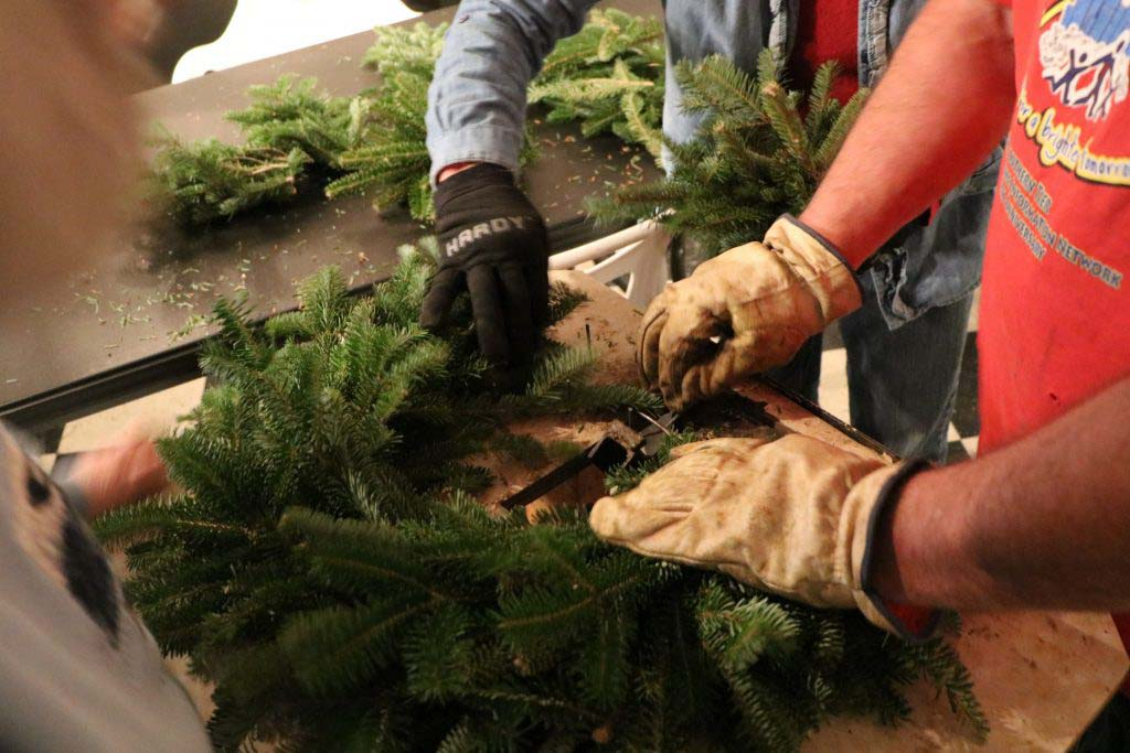 gloved hands form a Christmas wreath out of pine boughs