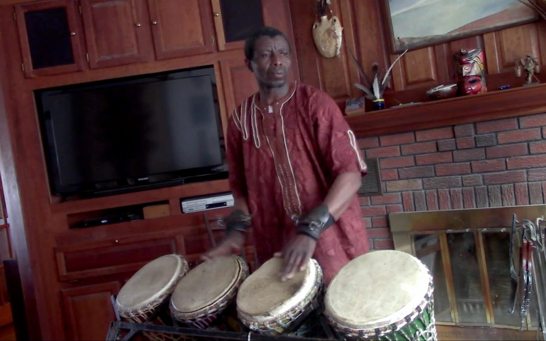 A Gambian man in traditional dress plays four drums indoors