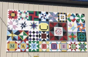 A collection of many smaller decorated squares. The last row of squares spells out Mayfield.