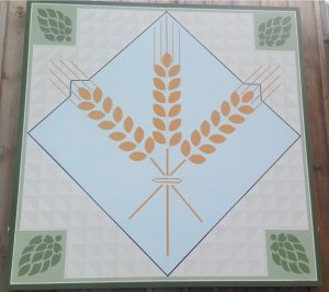A square featuring three barley leaves intertwined. Behind the leaves is a blue square. at each corner there is a green hop bud