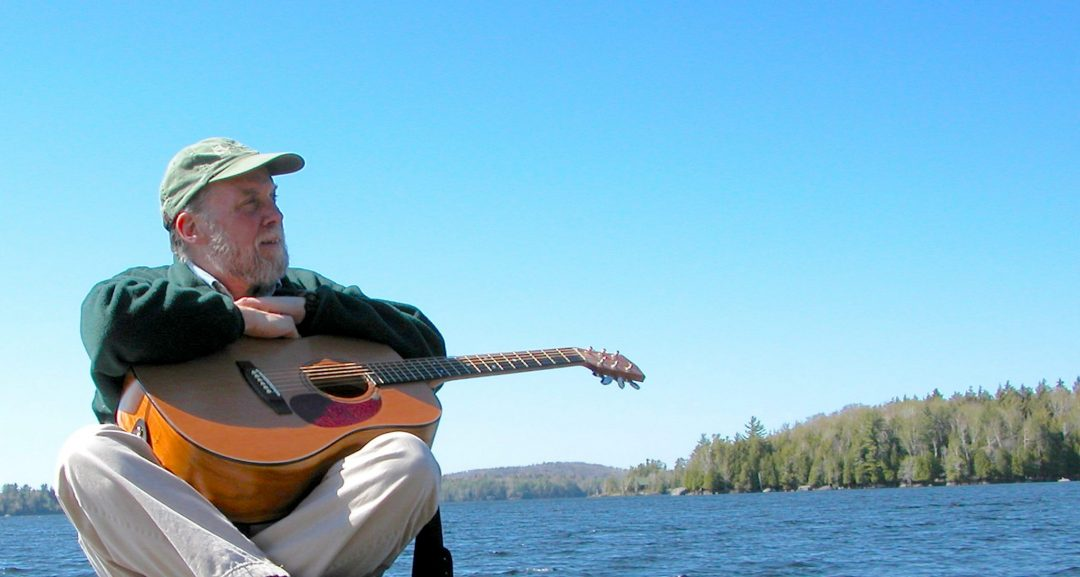 Dan Berggren with tan baseball cap, green sweater, and acoustic guitar sits cross legged with an Adirondack Lake behind him