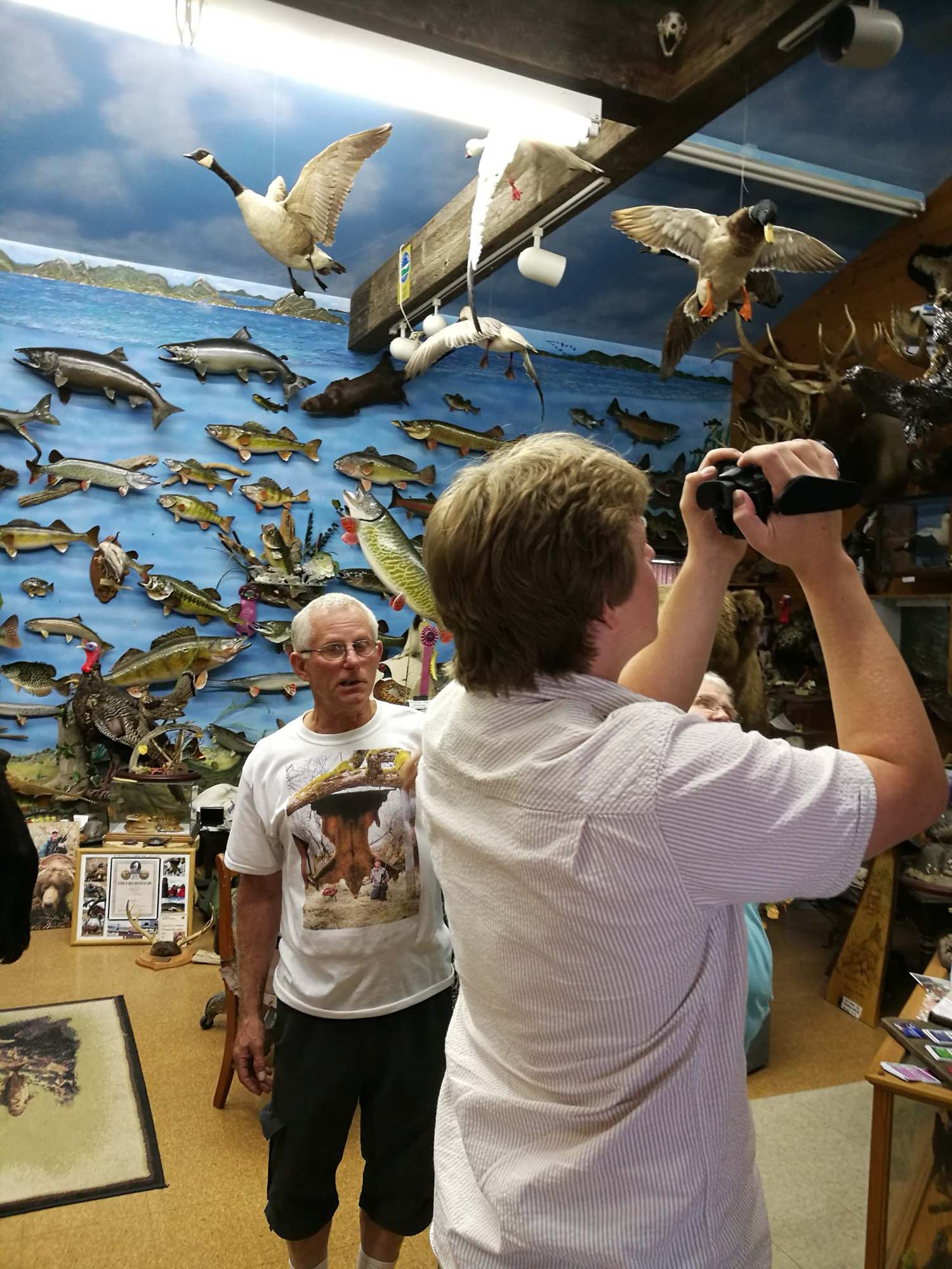 Joel Chapman uses a camcorder in a room with stuffed fish on the wall