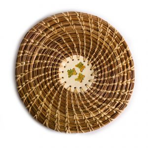 Decorative circular coaster made of pine needles and straw
